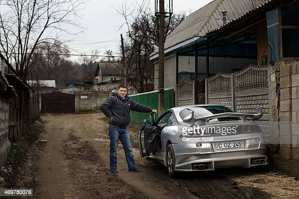 A man poses beside his tuned car in a poor district on March 15 2015 in Chisinau Moldova About 35 million inhabitants the Republic of Moldova is a...