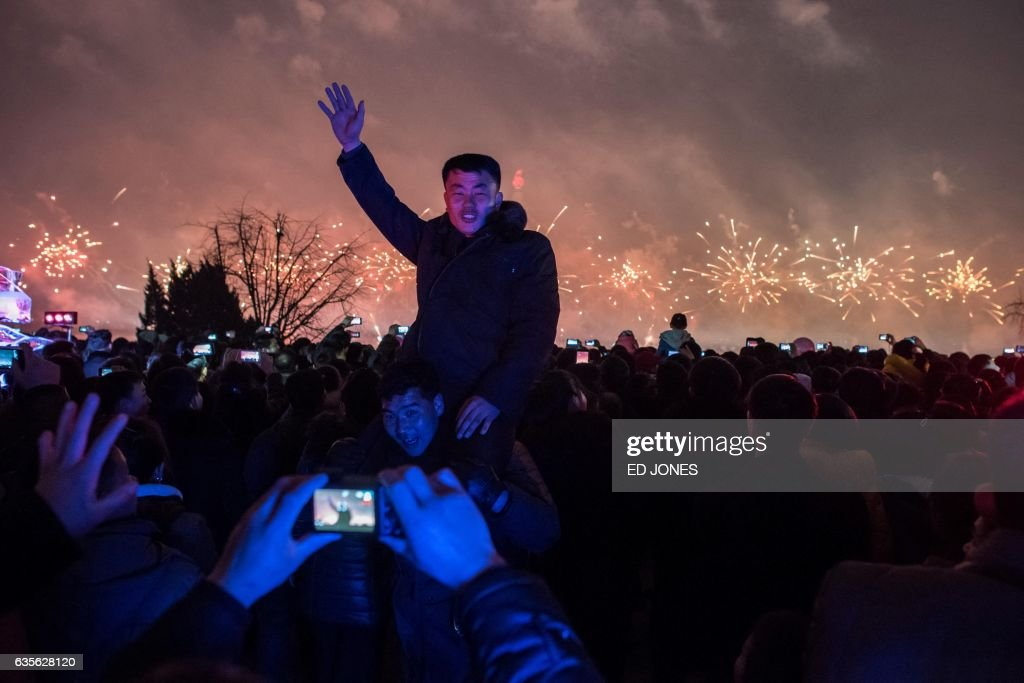 TOPSHOT - A man poses for a photo as people watch a fireworks display near the Taedong river, on the occasion of the 75th anniversary of the birth of Kim Jong-Il, in central Pyongyang on February 16, 2017. North Korean newlyweds, soldiers and children lined up to laud their country's rulers on February 16, the birthday of the late Kim Jong-Il, father of both the current leader and the exiled renegade assassinated in Malaysia this week. / AFP PHOTO / Ed JONES