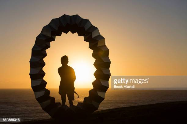 A man poses for a photo at sunrise by the work entitled 'Foci' by Karl Meyer at Sculpture By The Sea at Bondi Beach on October 19 2017 in Sydney...