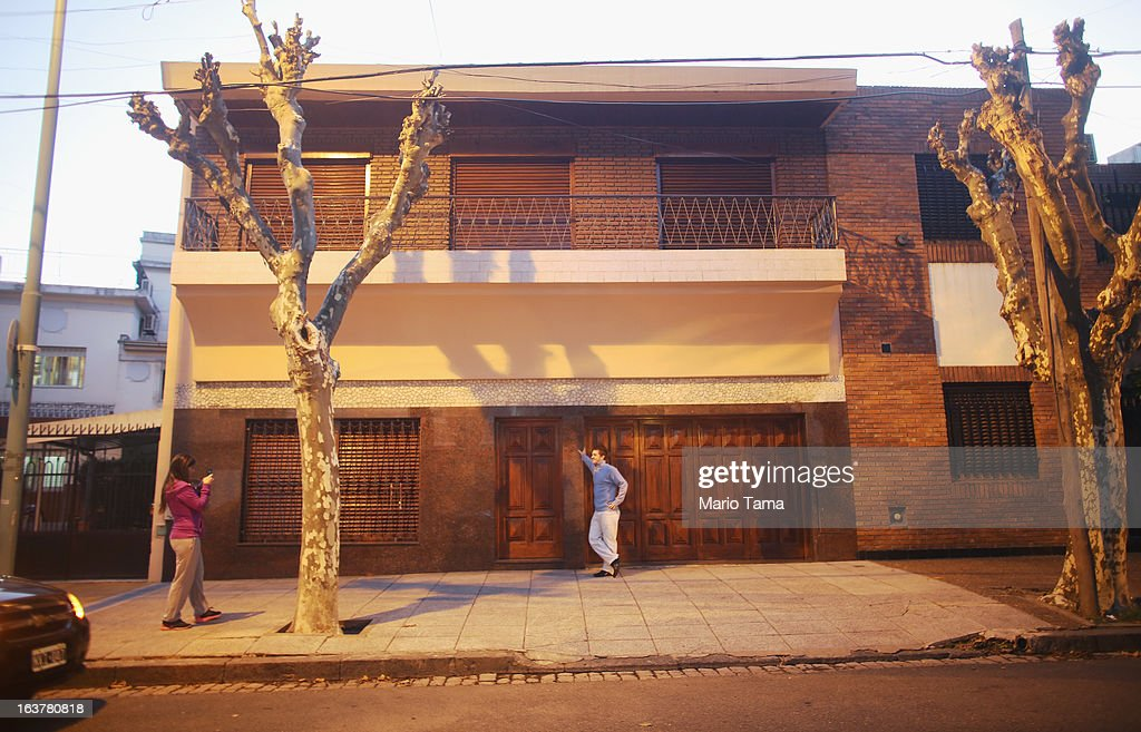 A man poses for a photo in front of the property where Pope Francis grew up (the original structure was destroyed) two days after Pope Francis was elected at the conclave on March 15, 2013 in Buenos Aires, Argentina. Francis was the archbishop of Buenos Aires and is the first pope to hail from South America.