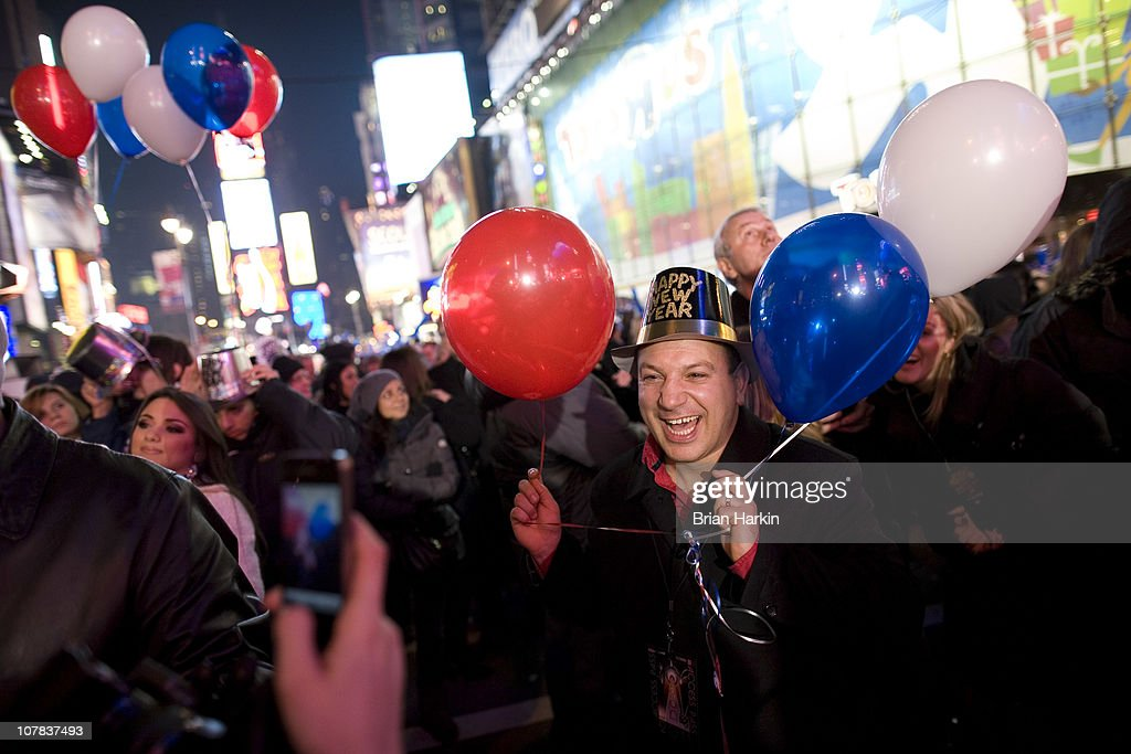 A man poses for a photo just before the annual ball drop December 31, 2010 in New York City. This year a 11,875-pound Waterford crystal ball descended a 141-foot tall flagpole to mark the beginning of 2011.