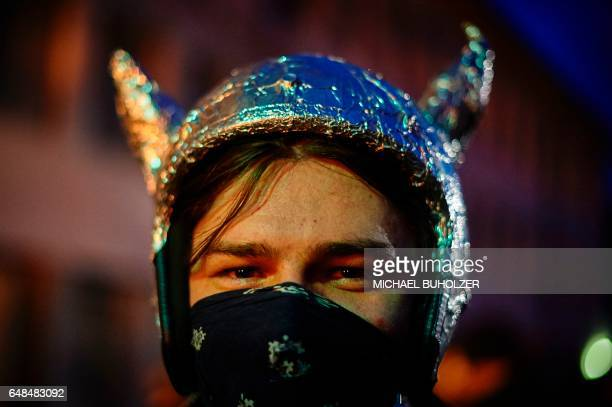 A man poses for a photograph before the 'Chienbase' procession on March 5 2017 evening in Liestal northern Switzerland The procession takes place on...