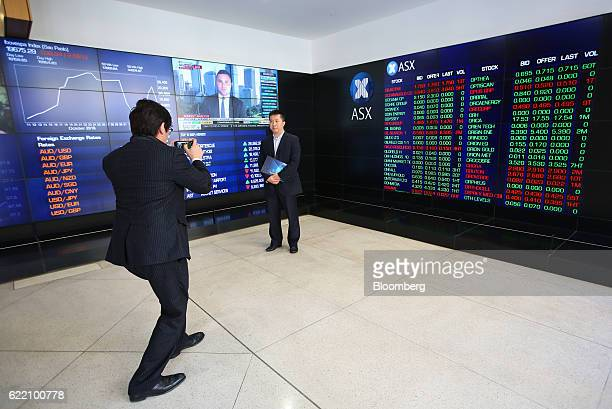 A man poses for a photograph in front of electronic boards displaying stock information inside the Australian Securities Exchange operated by ASX Ltd...