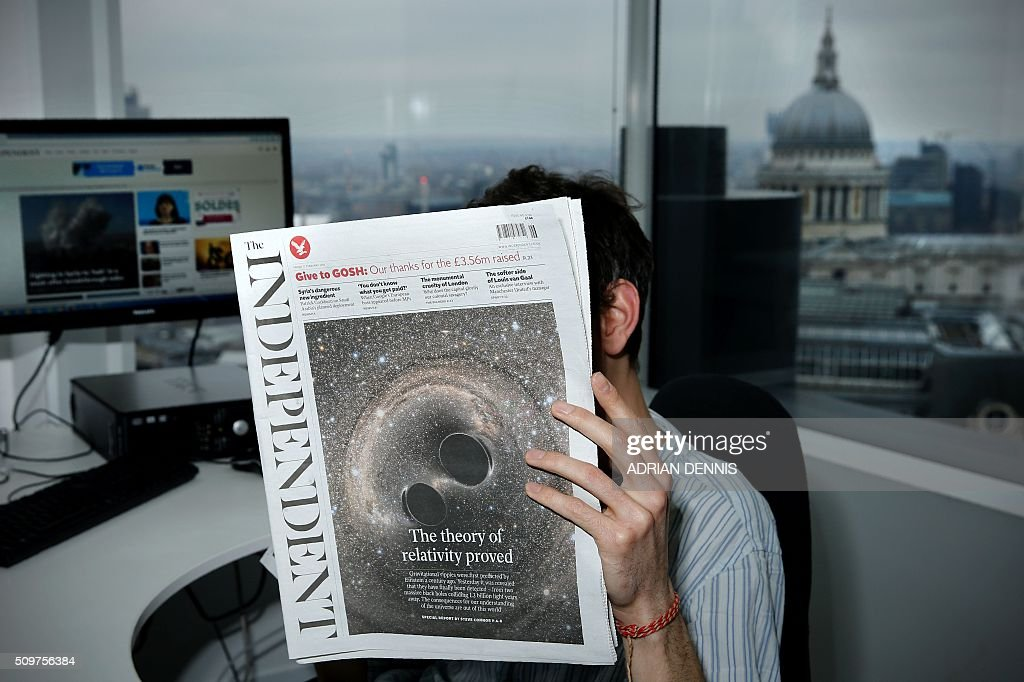 A man poses for a photograph with a copy of the British newspaper 'The Independent' in an office overlooking St. Paul's Cathedral in London on February 12, 2016. British newspaper The Independent will become digital only, and its last print edition will come out on March 26, owners ESI Media said in a statement. / AFP / ADRIAN DENNIS