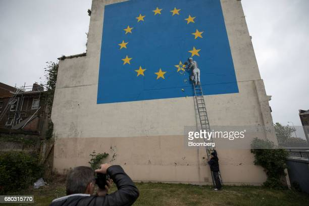 A man poses for a photograph with a mural depicting a European Union flag being chiseled by a workman on the side of a disused building near the...