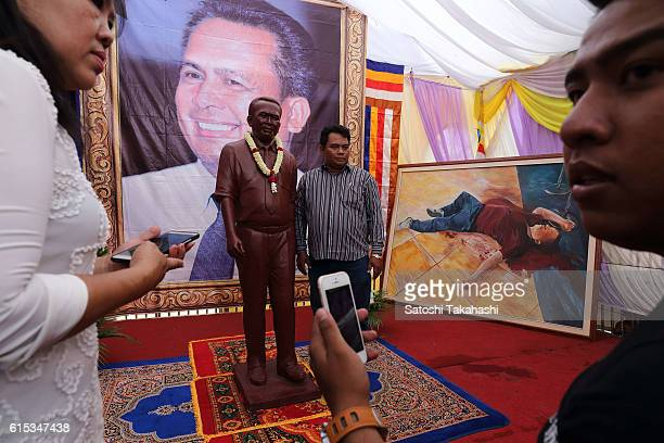 A man poses for a photograph with a statue of prominent political analyst Kem Ley during his 100day funeral ceremony Kem Ley was shot dead at Caltex...