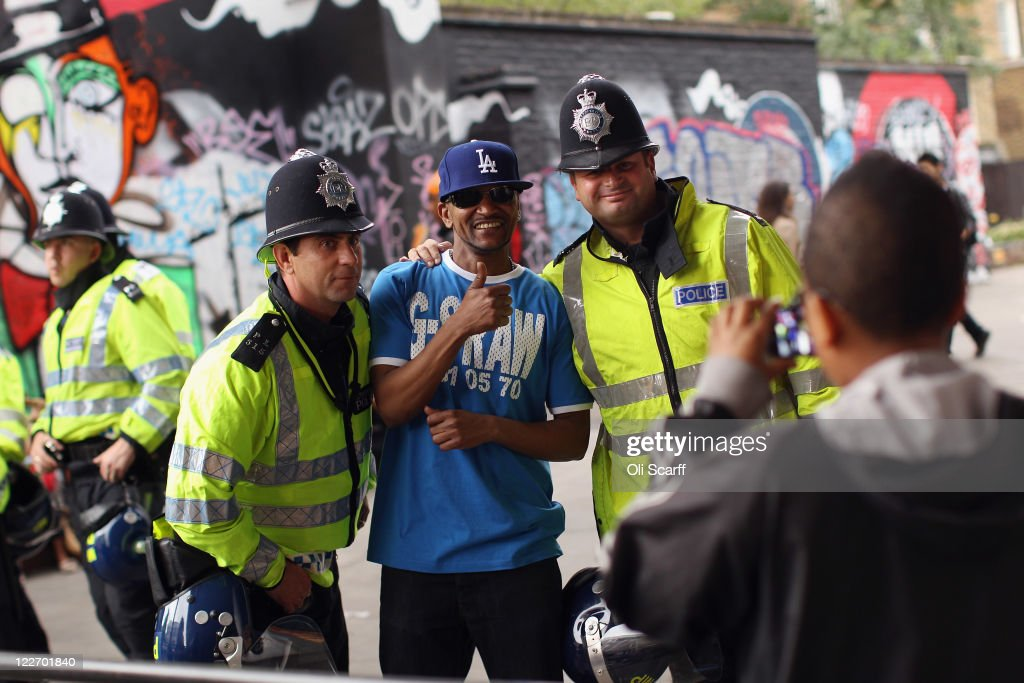 A man poses for a photograph with police officers at the Notting Hill Carnival on August 28, 2011 in London, England. The annual carnival, which is the largest of its kind in Europe and is expected to attract around 1 million revellers, has taken place every August Bank Holiday since 1966.
