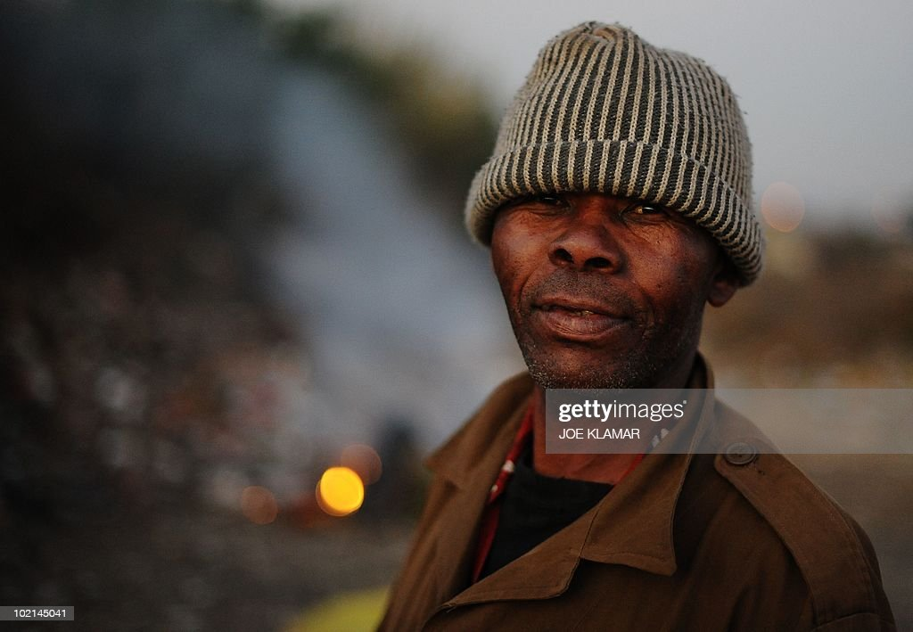 A man poses for a picture at a dumpster near Mamelodi township in Pretoria on June 16, 2010 during the 2010 World Cup football tournament in South Africa.