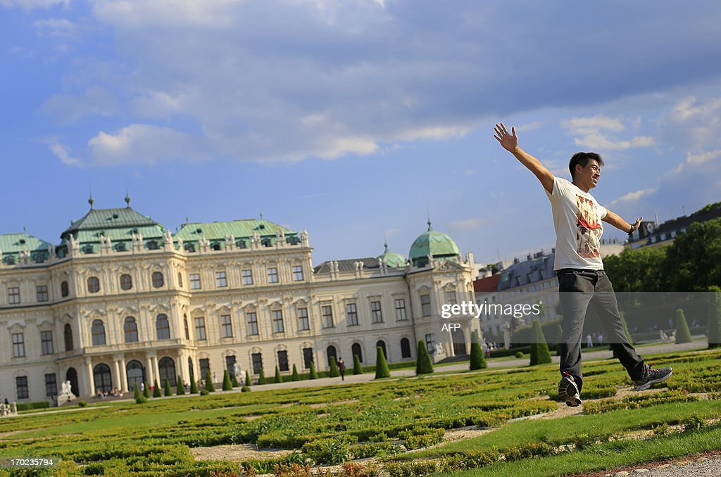 A man poses for a picture in the garden of the Belvedere Palace in Vienna on June 9, 2013. Meteorologists forecast temperatures around 25 degrees for central Austria. AFP PHOTO / ALEXANDER KLEIN