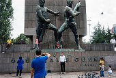 A man poses for a picture next to children feeding pigeons in front of the Guven Monument off the main Kizilay Square in Ankara on July 20 2016...