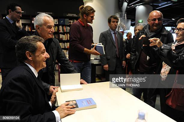A man poses for a picture with Nicolas Sarkozy former French president and head of the Les Republicains main opposition party as he signs copies of...