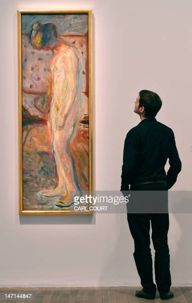 A man poses for photographers next to a painting by Norwegian artist Edvard Munch entitled 'Weeping Woman' during the press preview for the 'Edvard...