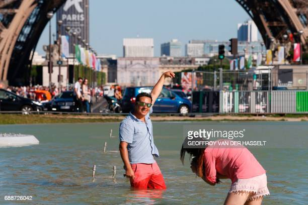 A man poses for photographs in the water of the Fountain of Warsaw at the Gardens of the Trocadero with the Eiffel Tower on the back ground during...