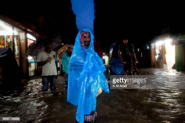 OLD DHAKA DHAKA BANGLADESH Man poses for picture covered with plastic when heavy rainfall made waterlogging in Dhaka city The death toll rises to 150...
