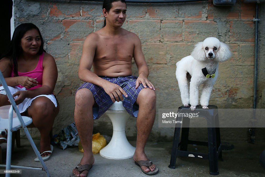 A man poses his dog in the occupied Complexo da Mare, one of the largest 'favela' complexes in Rio, on April 19, 2014 in Rio de Janeiro, Brazil. The Brazilian government has deployed nearly 3,000 federal troops to occupy the group of violence-plagued slums ahead of the June 12 start of the 2014 FIFA World Cup. The group of 16 communities house around 130,000 residents and had been dominated by drug gangs and militias. Mare is located close to Rio's international airport and has been mentioned as a likely pacification target for the police amid the city's efforts to improve security ahead of the 2014 FIFA World Cup and Rio 2016 Olympic Games.