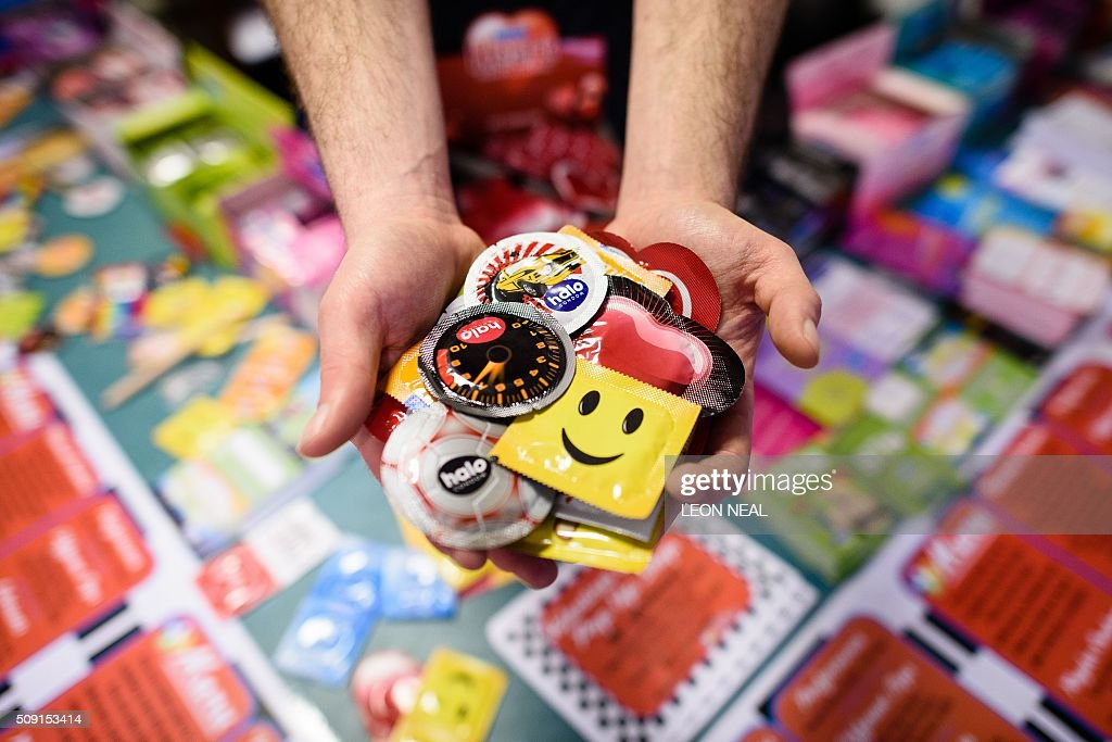 A man poses holding a selection of unusual condoms are displayed at the Valentine's Condom pop-up shop in east London on February 9, 2016. 'Come Correct' are hosting a free pop-up shop leading up to Valentine's day from February 8-13. Come Correct is the London-based condom distribution service where young people can access free condoms using a special 'c-card' in many locations across the capital. The scheme is run by the young people's charity Brook and has over 80 locations across the borough of Hackney where young people can pick up free contraceptives. The condoms are available in a huge range of colours and flavours including 'Blueberry Blast', apple, 'Mint Tingle' and 'Bubblegum Blast'. / AFP / LEON NEAL