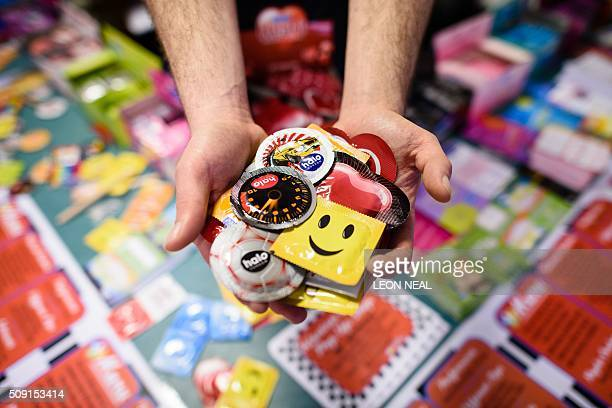 A man poses holding a selection of unusual condoms are displayed at the Valentine's Condom popup shop in east London on February 9 2016 'Come...