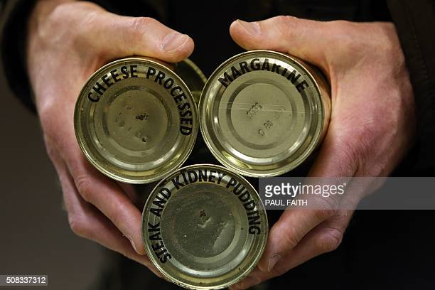 A man poses holding tinned food inside the nuclear bunker on the outskirts of Ballymena in Northern Ireland on February 4 2016 owned by the Office of...
