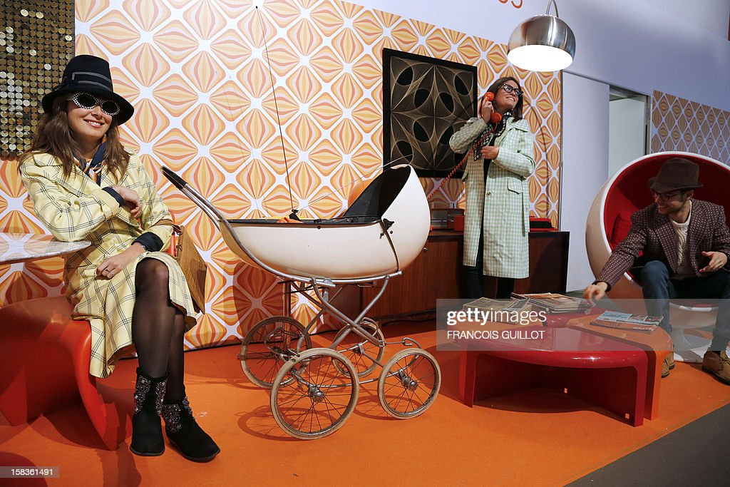 A man poses in a arm-chair (R) designed by Danish Verner Panton (1926-1998) during the exhibition entitled 'Le train, reflet de son époque' dedicated to vintage furniture and other items, on December 14, 2012, at the Paris saint-Lazare railway station. This event takes part on the fringe of the display of the 'Petit gris' suburban train's items to be auctioned on December 18 in favour of the French charitable organisation 'Les Restos du Coeur' (Restaurants of the Heart) in Paris. France national rail company SNCF is set to offer more than 150 vintage items of the last Z6100 series trains from the 1960's.