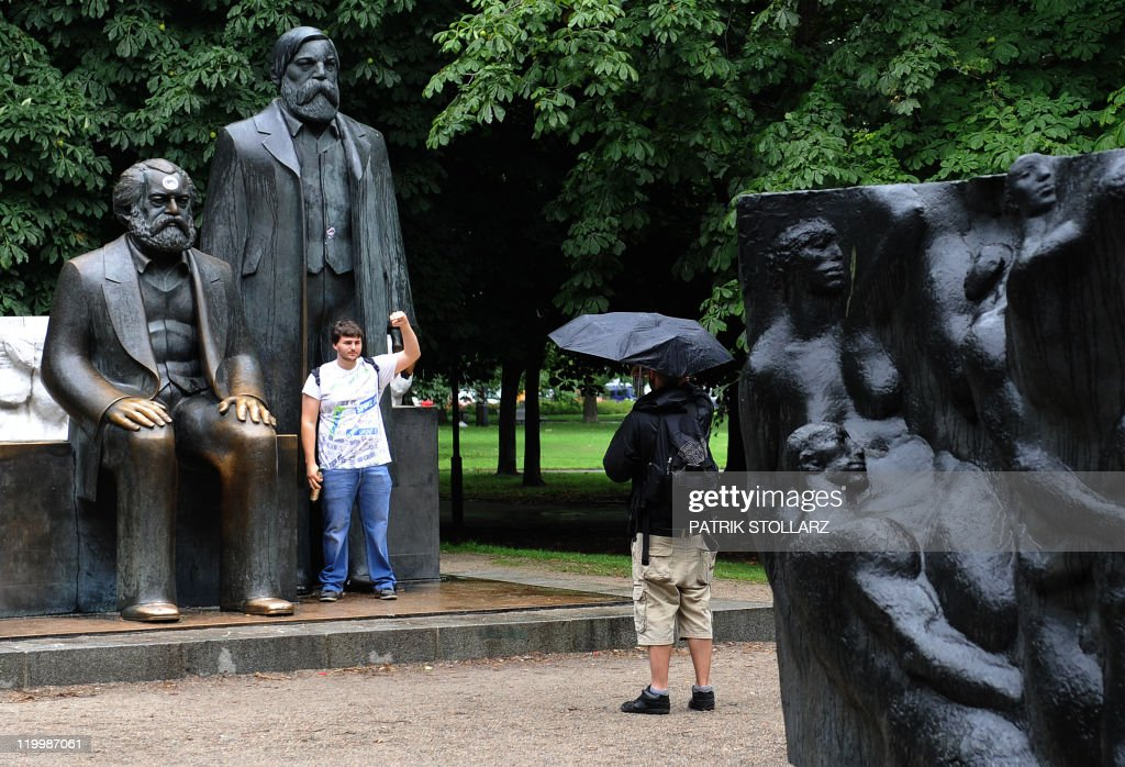 A man poses in front of a bronze statue of German philosopher, sociologist and economic historian Karl Marx (L) and German industrialist and social scientist Friedrich Engels on July 28, 2011 in Berlin. The monument has become an icon of the early communism ideology. It was built by east German sculptor Ludwig Engelhardt and inaugurated in 1986.