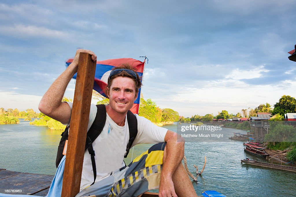 A man poses in front of a Laos flag : Stock Photo