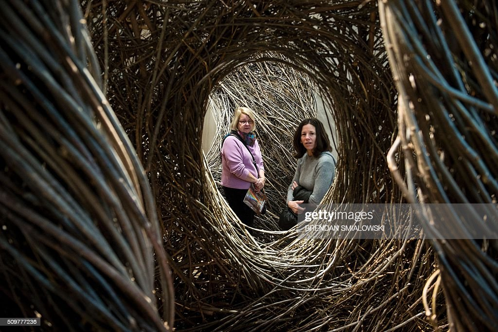 A man poses in Patrick Dougherty's Shindig at the Smithsonian's Renwick Gallery February 12, 2016 in Washington, DC. / AFP / Brendan Smialowski / RESTRICTED TO EDITORIAL USE - MANDATORY MENTION OF THE ARTIST UPON PUBLICATION - TO ILLUSTRATE THE EVENT AS SPECIFIED IN THE CAPTION