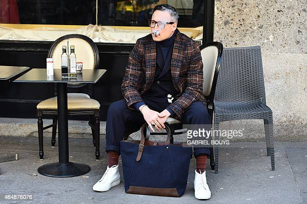 A man poses in the street before the Dolce Gabbana fashion show during the women Fall / Winter 2015/16 Milan's Fashion Week on March 1 2015 AFP PHOTO...