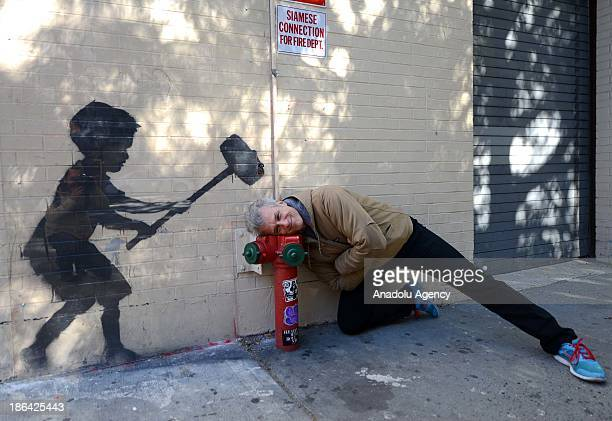 A man poses near a picece of graffiti artist and activist Banksy's ongoing ''Better Out Than In'' series on October 28 2013 in New York City United...