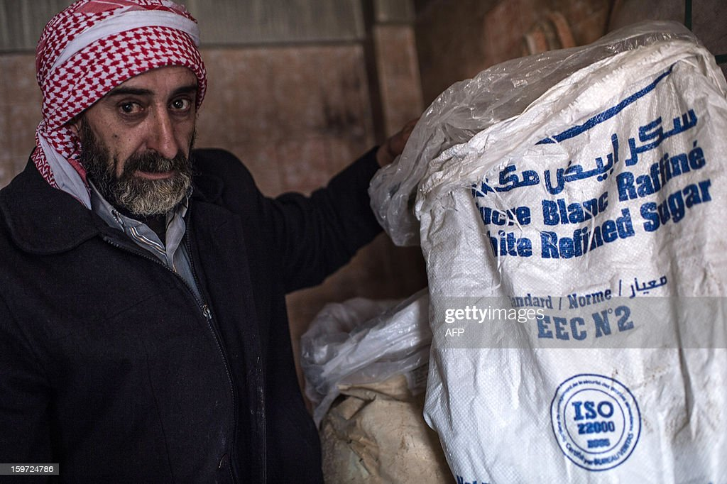A man poses near white refined sugar that he uses to produce hand made missiles in a secret factory on January 19, 2013 in Al-Bab, 30 kilometers from the northeastern Syrian city of Aleppo. Recycled or non explosed bombs recolted after shellings are used for the manufacturing and sugar as well for the propulsion. Each day, nearly 50 missiles are assembled for the Abu baker Brigade. AFP PHOTO/EDOUARD ELIAS