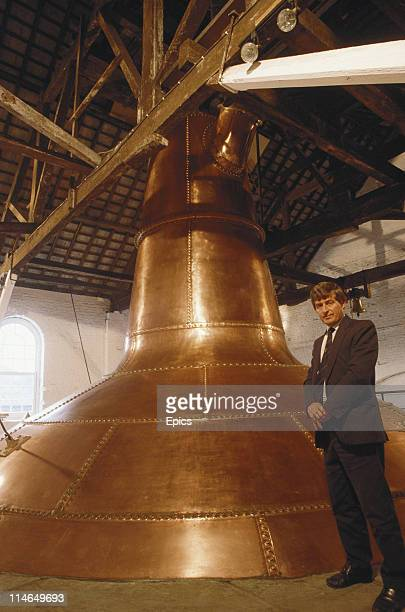 A man poses next to a huge copper pot still used in the fermenting process to make whiskey at the distillery in Midelton County Cork Ireland circa...