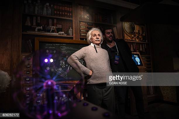 A man poses next to a wax statue of Germanborn physicist Albert Einstein on November 22 2016 at the world's 21st Madame Tussauds wax museum in...