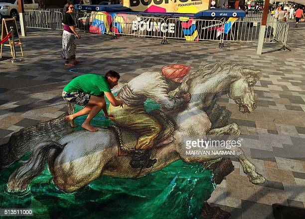 A man poses on a 3D artwork on March 3 2016 near the Jumeirah Beach Residence in Dubai during the Canvas Festival a threedimensional pavement art...