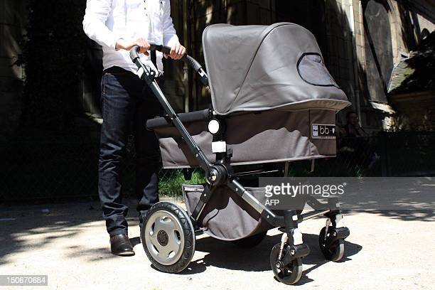 A man poses with a baby buggie on July 17 2012 in a park in Paris Baby buggies reinvented as sleek hightech designer objects have become boy's toys...