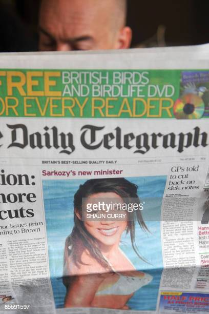 A man poses with a copy of Britain's Daily Telegraph newspaper featuring a picture of French television presenter Christine Kelly in London on March...