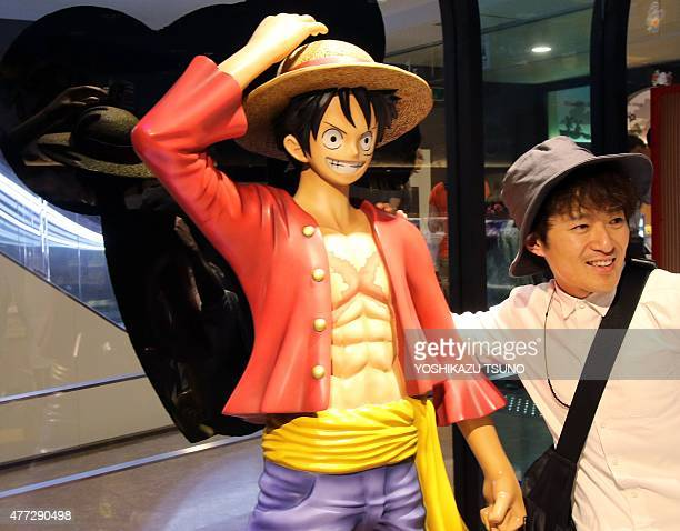 A man poses with a figure of Monkey D Luffy a main character of Japanese cartoon 'One Piece' in Tokyo on June 16 2015 Japanese comic artist Eiichiro...