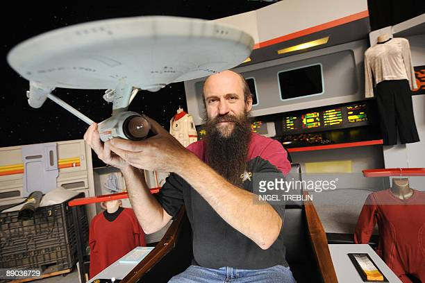 A man poses with a model of the 'Starship Enterprise' on the reproduction of the Enterprise's bridge at the 'Filmwelt Center' in the northern German...