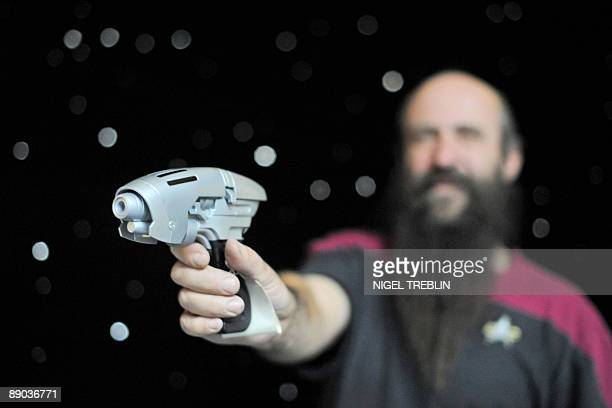 A man poses with a NX01Phaser on a reproduction of the Starship Enterprise's bridge at the 'Filmwelt Center' in the northern German city of Lauenau...