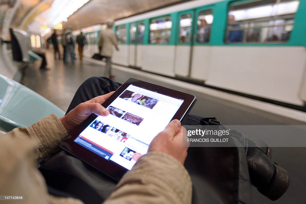 A man poses with a tablet on June 26, 2012, in the Parisian metro, on the inauguration day of a free Wi-Fi access available in forty-six Paris' public transportation sites including platforms of three underground stations.