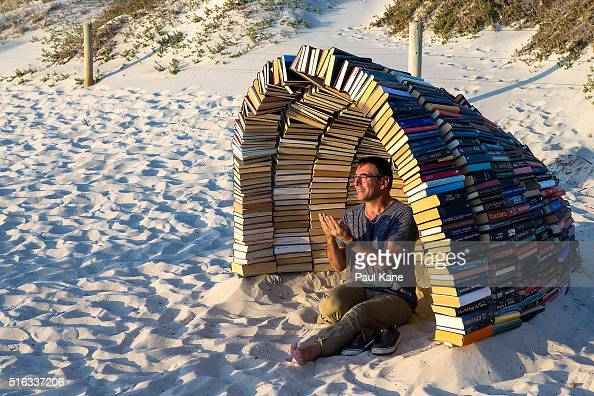 A man poses with 'Book Cave' by artist Juliet Lea during Sculpture By The Sea 2016 at Cottesloe Beach on March 18 2016 in Perth Australia