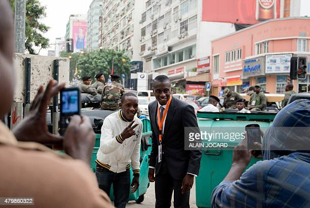 A man poses with French international and Paris SaintGermain football player Blaise Matuidi in Luanda on July 3 2015 Matuidi is following French...