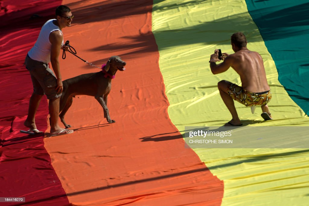 A man poses with his dog during the gay pride parade at Copacabana beach in Rio de Janeiro, Brazil on October 13, 2013.