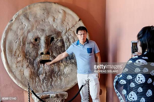A man poses with his hand inside the Bocca della Verita an ancient Roman marble disc with a relief carving of a man's face in downtown Rome on...