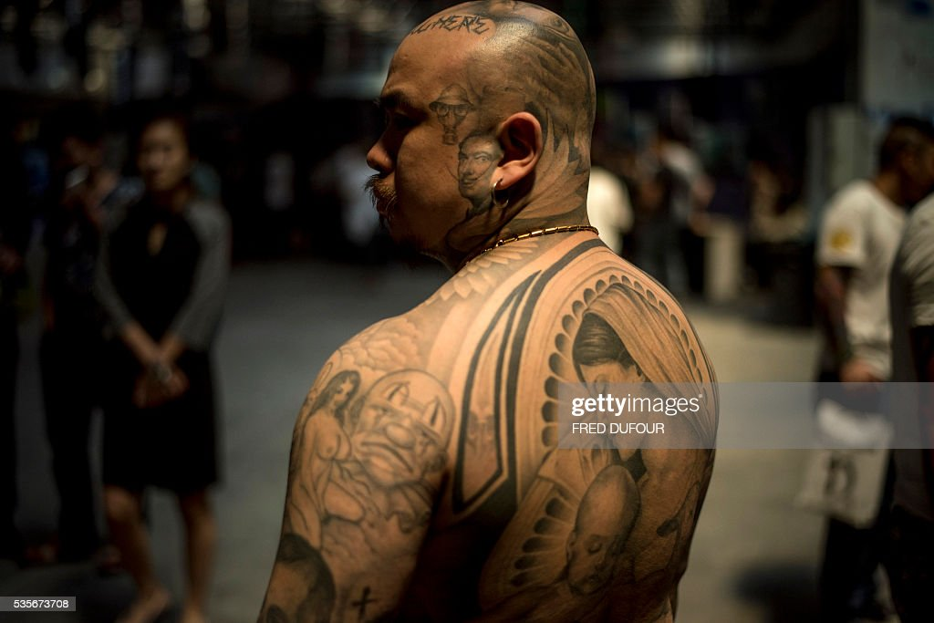 A man poses with tattoos at the Langfang International Tattoo show, in Hebei province, on May 29, 2016. / AFP / FRED