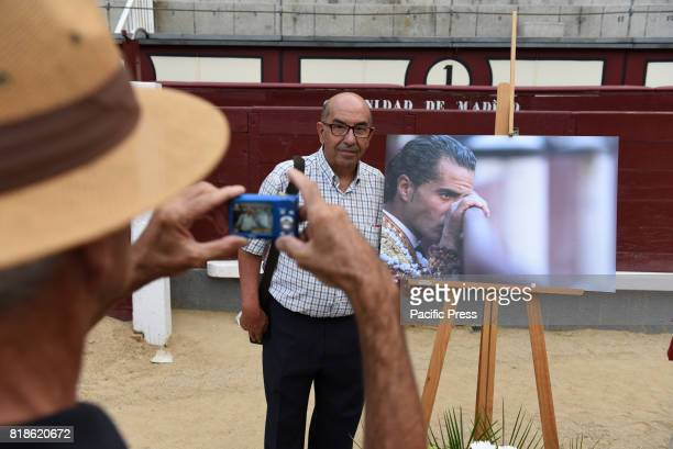 A man poses with the picture of Ivan Fandiño during a funeral mass at 'Las Ventas' bullring in Madrid
