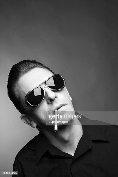 Man posing in sunglasses with cigarette