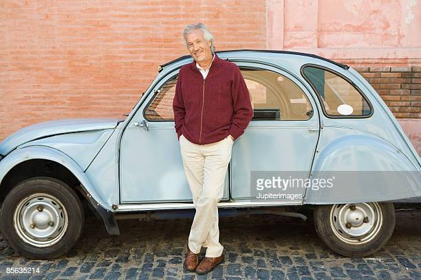 Man posing next to car