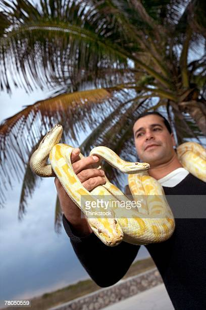 Man posing with snakes in Miami