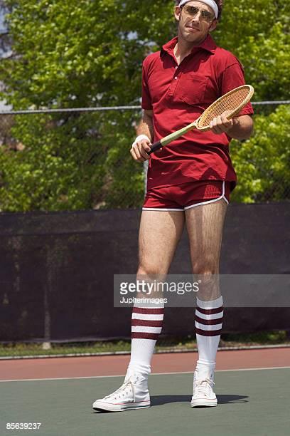 Man posing with tennis racquet on tennis court