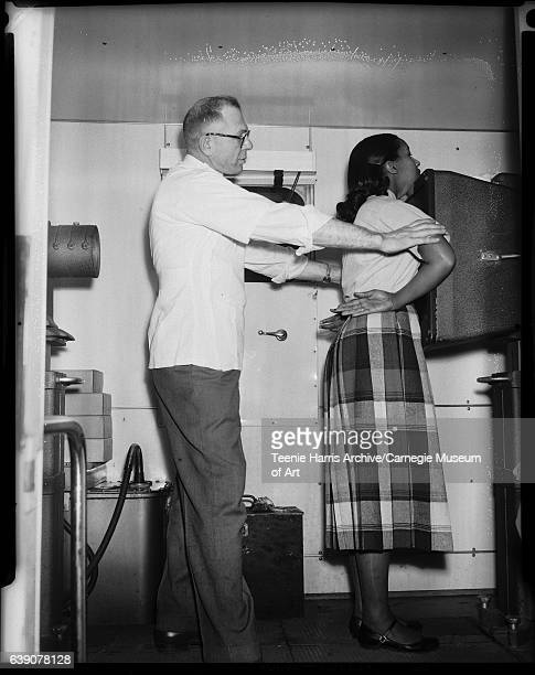 Man positioning woman in front of xray machine next to other machinery with tubes circa 19501960