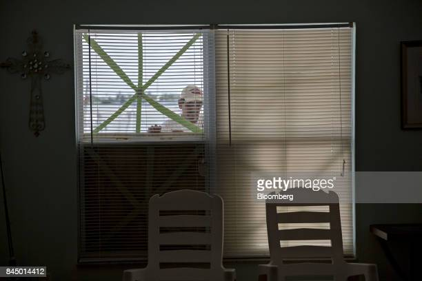 A man positions a piece of plywood over a window ahead of Hurricane Irma in Madeira Beach Florida US on Saturday Sept 9 2017 HurricaneIrmashifted...